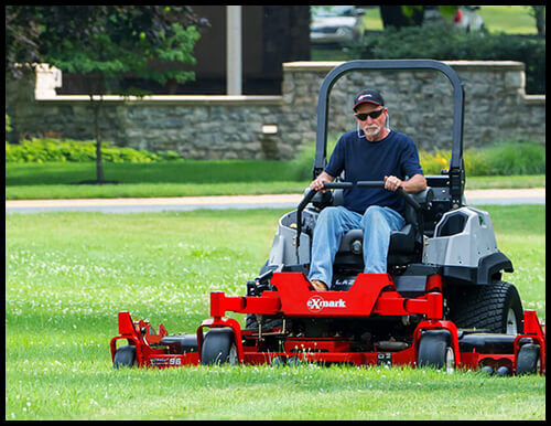 Man using a commercial Ex Mark lawn mower.