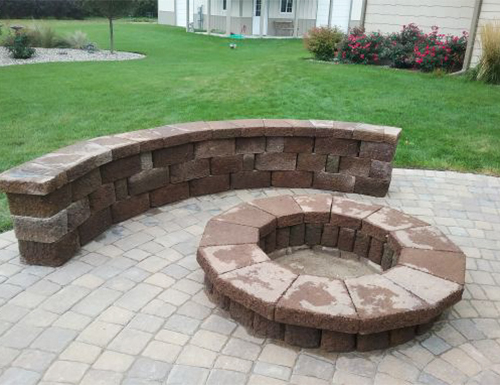 Newly finished bench and firepit in a backyard.