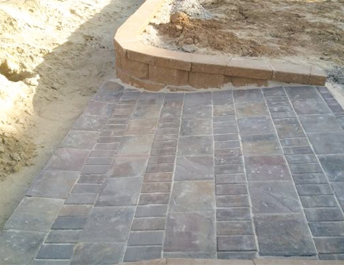 Ramp patio paver with small retaining wall.