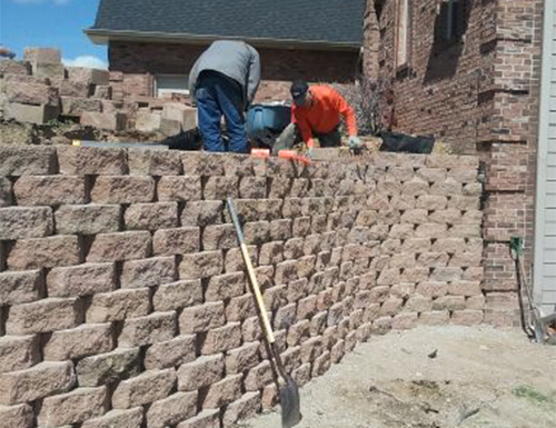 Two men working on a residential retaining wall.