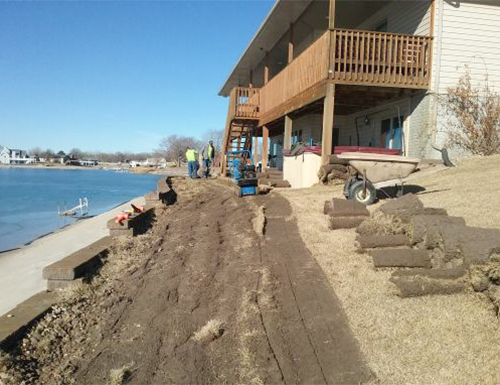 Finishing a retaining wall with sod.